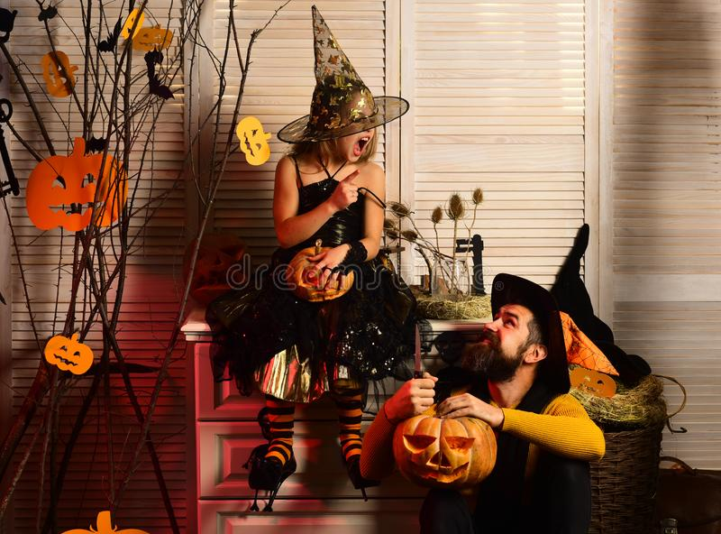 Father and daughter with Halloween decor. Wizard and little witch. In hats carve pumpkins. Girl and bearded men argue on spooky carnival room background royalty free stock images