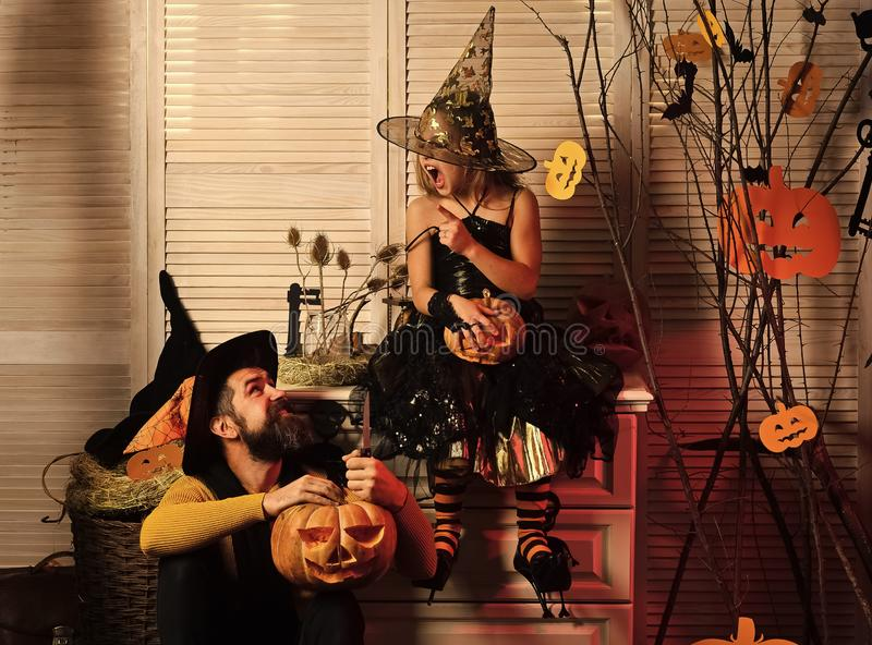 Father and daughter with Halloween decor. Wizard and little witch stock image