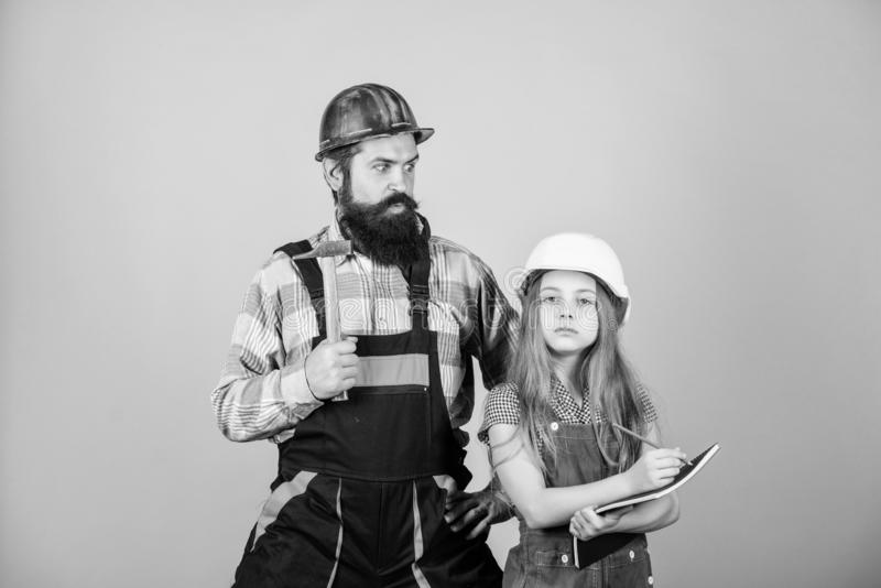Father and daughter hard hat helmet uniform renovating home. Home improvement activity. Kid girl planning renovation royalty free stock photo