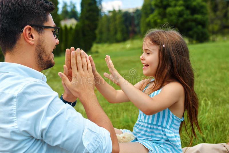 Father And Daughter Having Fun. Happy Dad Playing With Kid. Father And Daughter Having Fun. Happy Smiling Young Dad Playing Hand Clapping Game With His Kid royalty free stock images