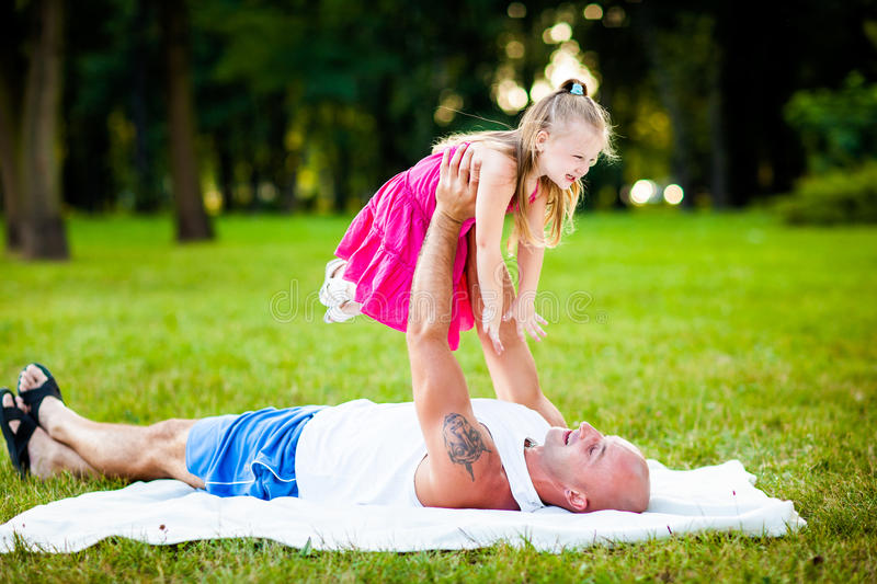 Father and daughter having fun in a park royalty free stock photography
