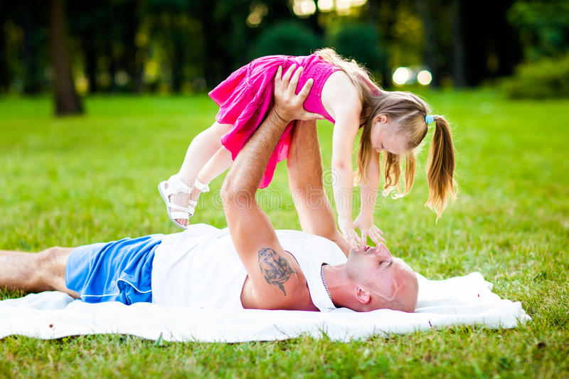 Father and daughter having fun in a park stock photography