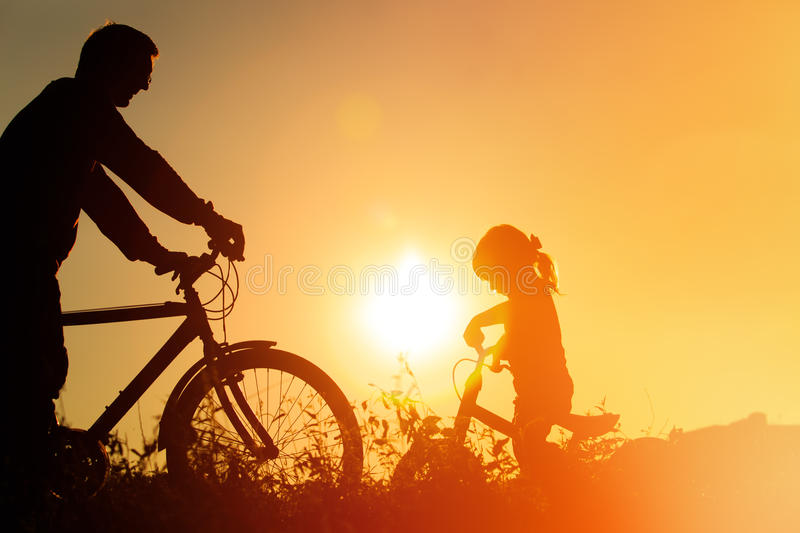 Father and daughter having fun riding bike at sunset, active family sport royalty free stock photos