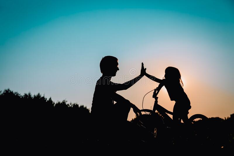 Father and daughter having fun riding bike at sunset stock images