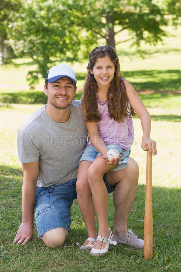 Father and daughter holding baseball bat in park royalty free stock image