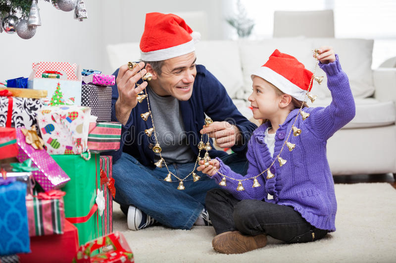 Father And Daughter Holding Christmas Ornaments stock images