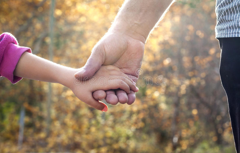 Father and daughter holding hand by hand stock image