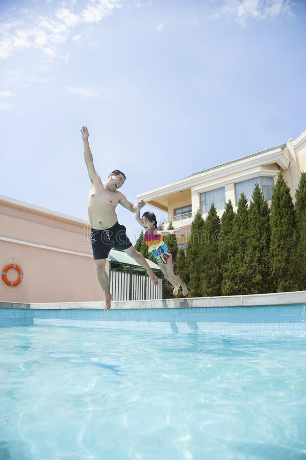 Father and daughter holding hands and jumping into the pool royalty free stock image