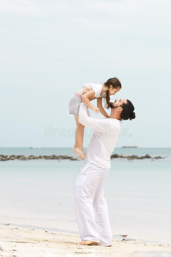 Father and daughter walking on deserted tropical beach. happy loving vacation stock image