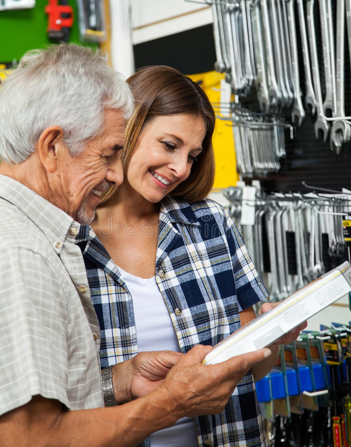 Father And Daughter Holding Tool Box. Happy father and daughter holding tool box in hardware shop royalty free stock images