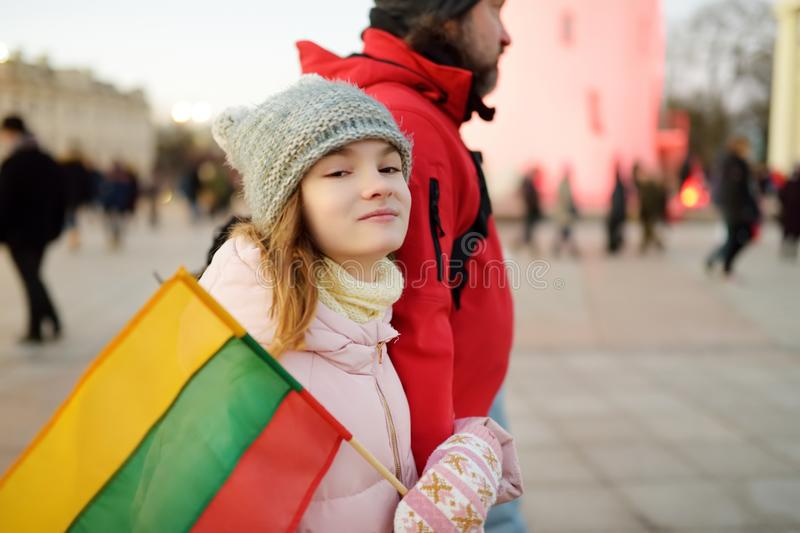 Father and daughter holding tricolor Lithuanian flag on Lithuanian Independence Day. Family celebrating national holiday royalty free stock photos