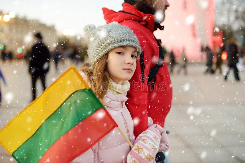 Father and daughter holding tricolor Lithuanian flag on Lithuanian Independence Day. Family celebrating national holiday stock photo