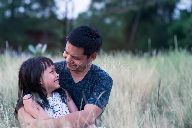 Father and daughter hugging in the green nature with love stock image
