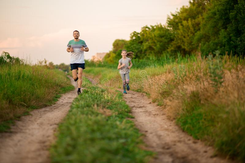 Father and daughter jogging. Cheerful father and daughter run in park together. Sport life concept royalty free stock photo