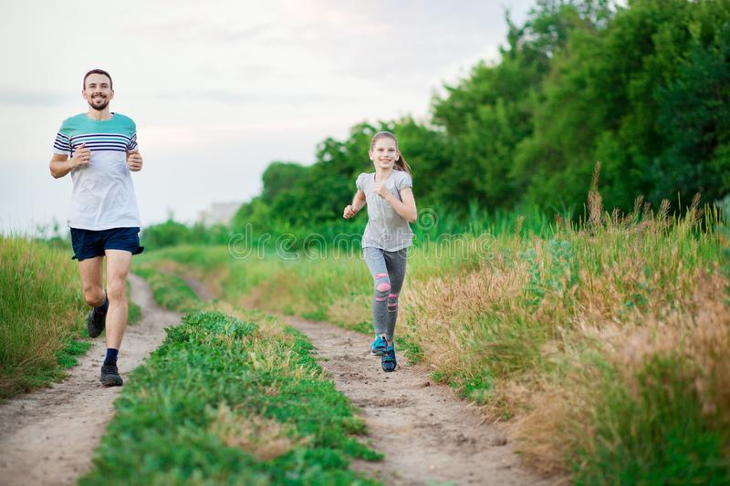 Father and daughter jogging. Cheerful father and daughter run in park together. Sport life concept royalty free stock photography