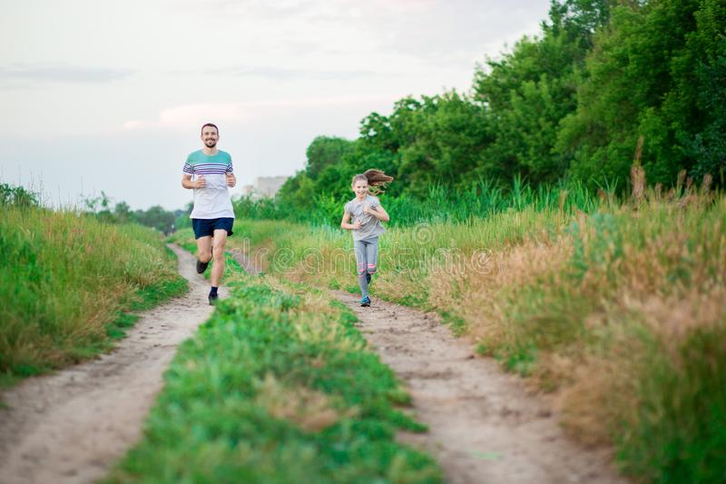 Father and daughter jogging. Cheerful father and daughter run in park together. Sport life concept stock photos