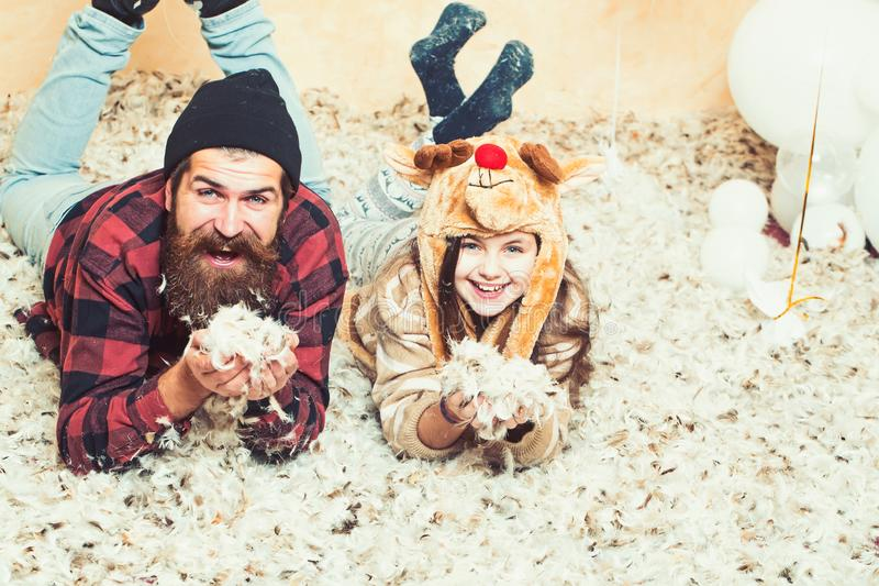 Father and daughter lie in feathers, christmas. Man hipster and child smile at xmas. Family holiday party. Fathers day stock photos