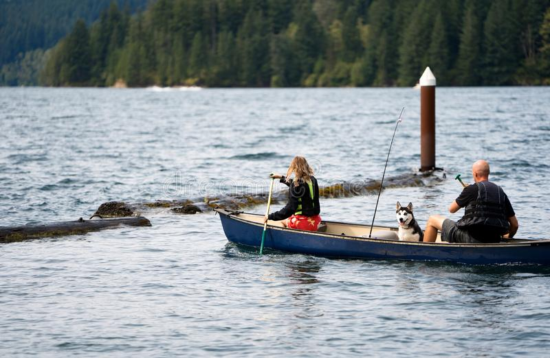 Father and daughter in life jackets and husky dog rowing in boat on the troubled Merwin Lake stock photo