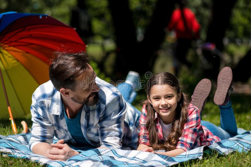 Father And Daughter Are Lying On The Blanket In The Park.Family Having Picnic. Colorful Umbrella On The Background. stock photography