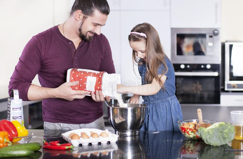 Father and daughter making meal together in kitchen. Cooking classes concept stock photos