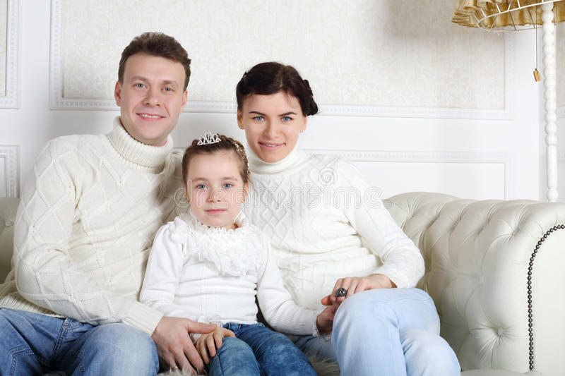 Father, daughter and mother in white sweaters and jeans sit. On sofa at home royalty free stock photography