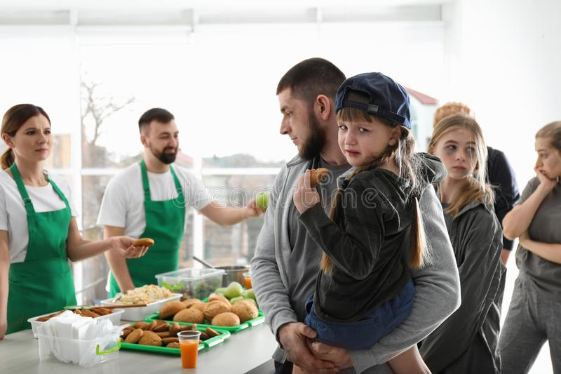 Father and daughter with other poor people receiving food from volunteers royalty free stock images