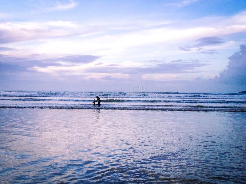 Father and Daughter Paddling in the Sea stock images