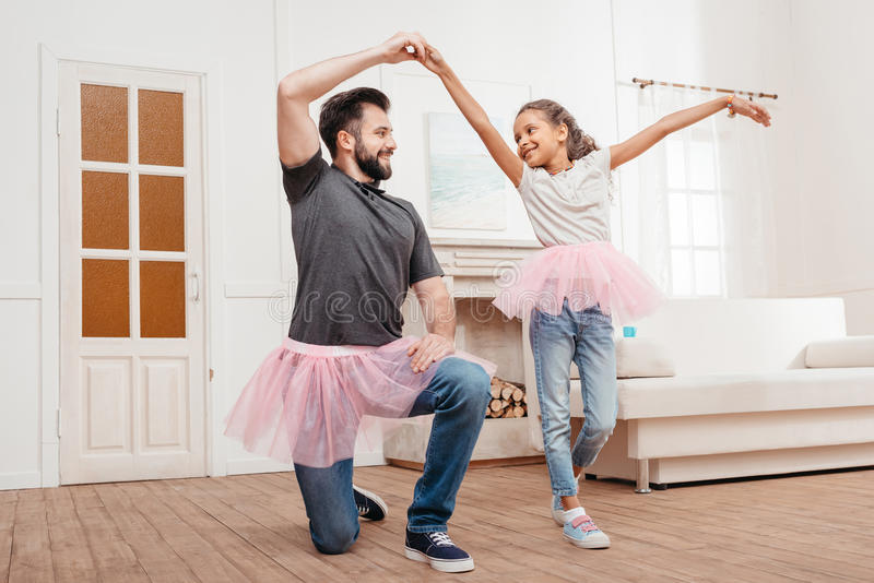 Father and daughter in pink tutu tulle skirts dancing at home. Multicultural father and daughter in pink tutu tulle skirts dancing at home stock photography
