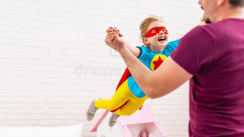 Father and daughter play superhero. The father circles the daughter imitating flight of the heroic child. The concept of a close-knit family. The child is stock photography