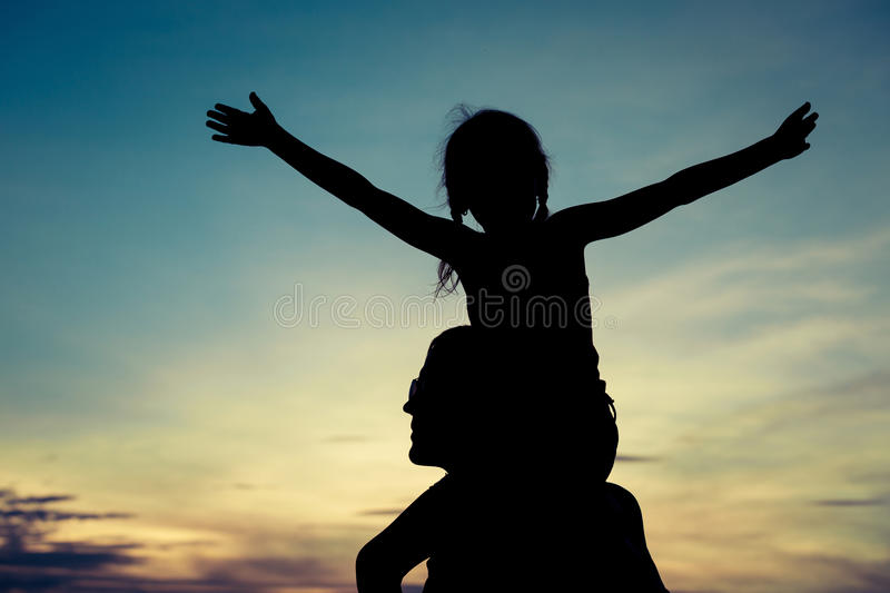 Father and daughter playing on the beach at the sunset time. stock photo