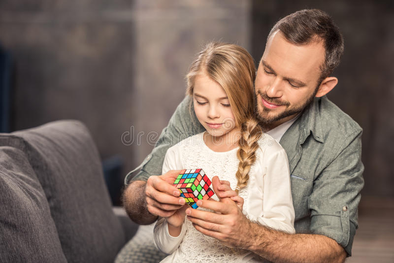 Father and daughter playing with cube stock images