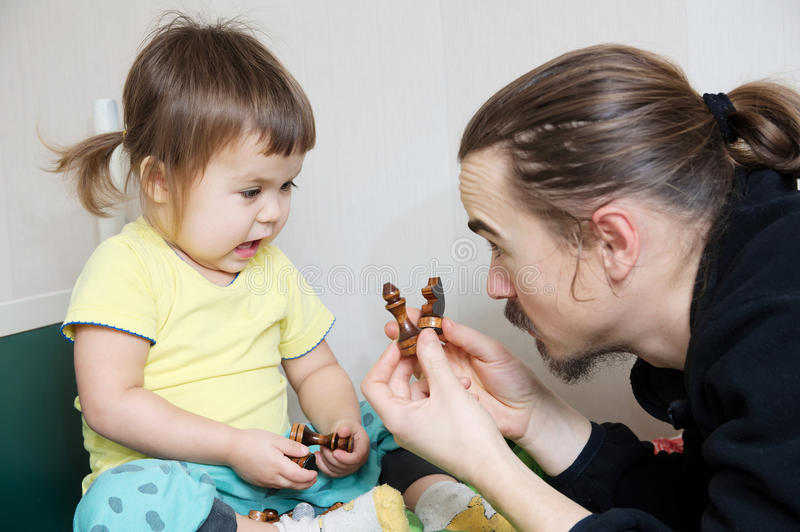 Father and daughter playing, dad teaching child chess figure. Names - children development concept stock photos