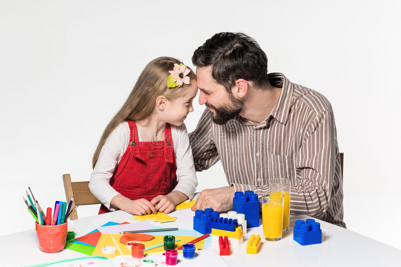 Father and daughter playing educational games together. Both smiling happily on the white background royalty free stock image