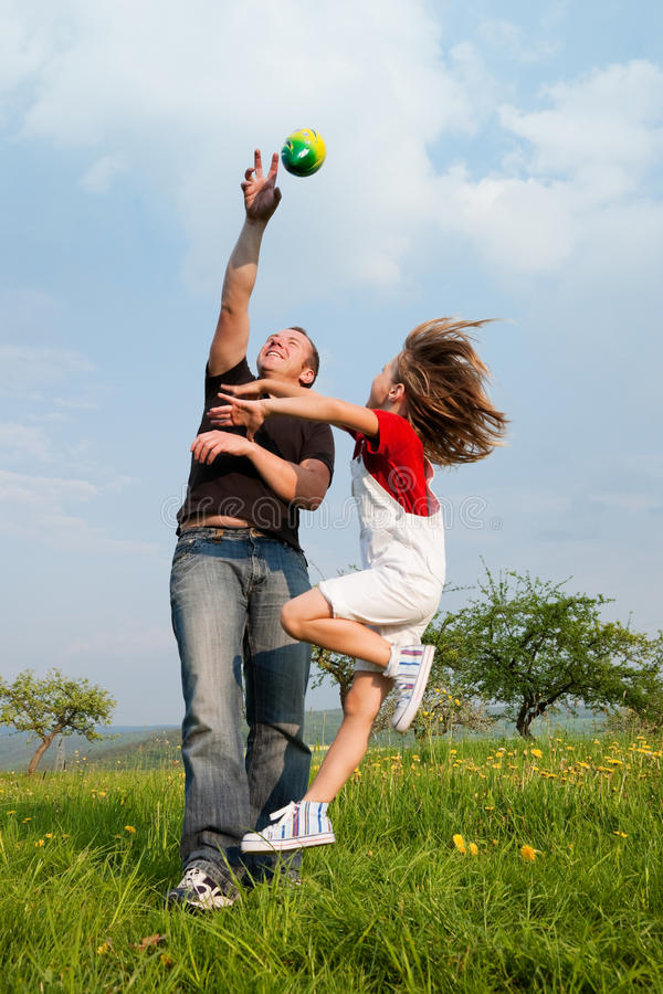 Father and daughter playing football on meadow royalty free stock image