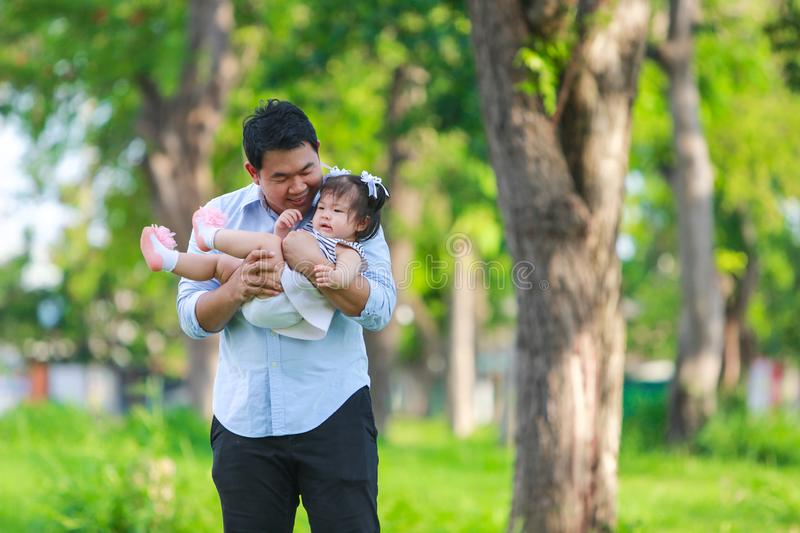 Father and daughter playing and running around the park royalty free stock photography