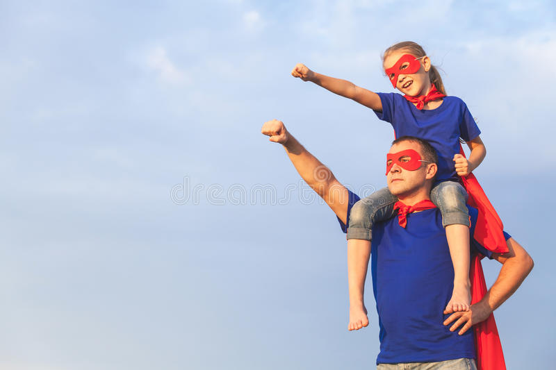 Father and daughter playing superhero at the day time. People having fun outdoors. Concept of friendly family royalty free stock photography