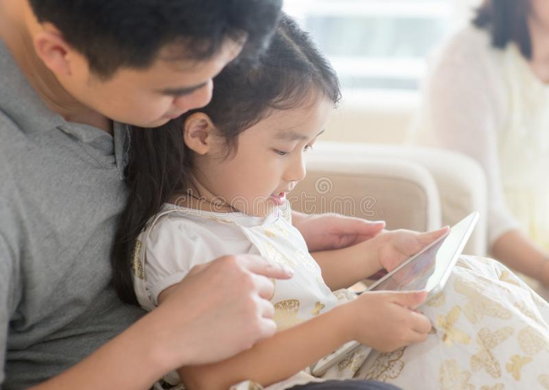 Father and daughter playing with tablet pc. royalty free stock image