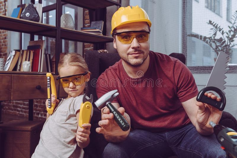 Father and daughter posing with plastic toy tools while making a wooden frame at home royalty free stock photos