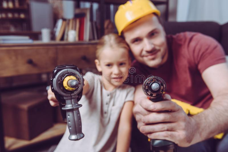 Father and daughter posing with toy drills while making a wooden frame at home royalty free stock photos