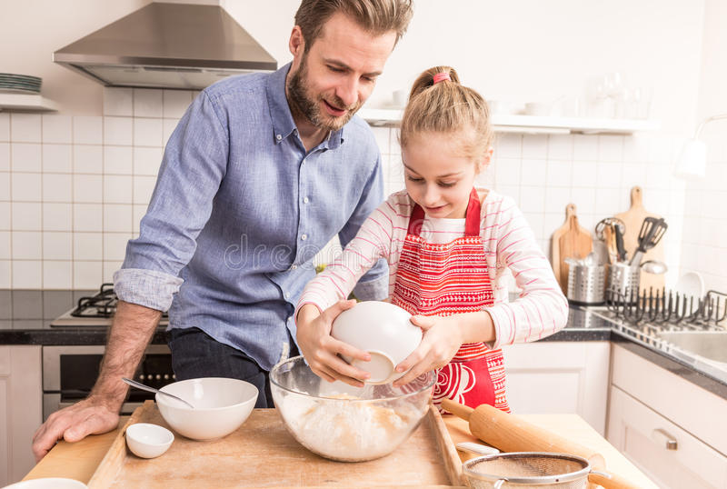 Father and daughter preparing cookie dough in the kitchen royalty free stock photo