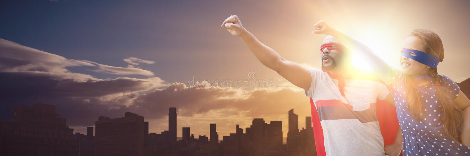 Composite image of father and daughter pretending to be superhero. Father and daughter pretending to be superhero against picture of city by sunrise royalty free stock image