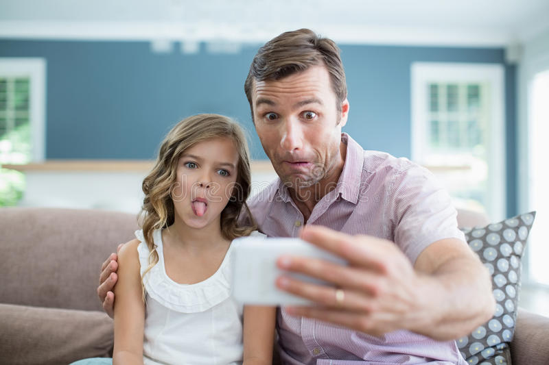 Father and daughter pulling funny faces while taking selfie in living room royalty free stock images