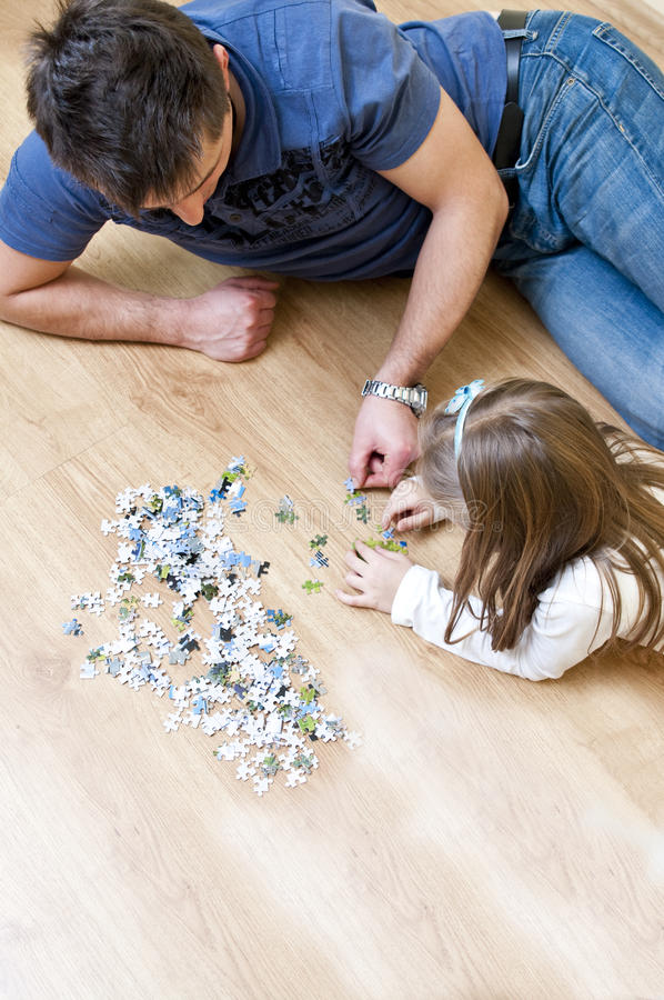 Father and daughter puzzle. Father arranging jigsaw puzzle with his daughter on hardwood floor stock photos
