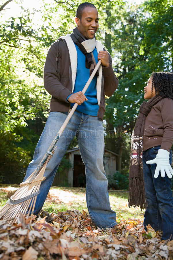 Father and daughter raking leaves royalty free stock image