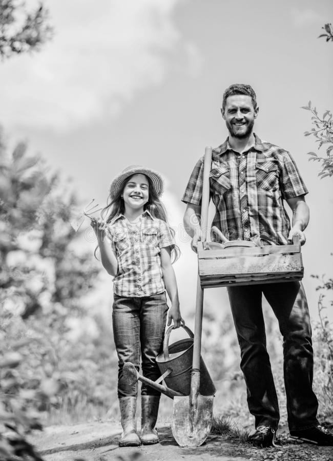 Father and daughter on rancho. summer farming. farmer man with little girl. garden tools, shovel and watering can. kid royalty free stock photography