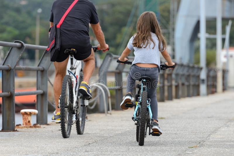 Father and daughter ride bikes, rear view stock image
