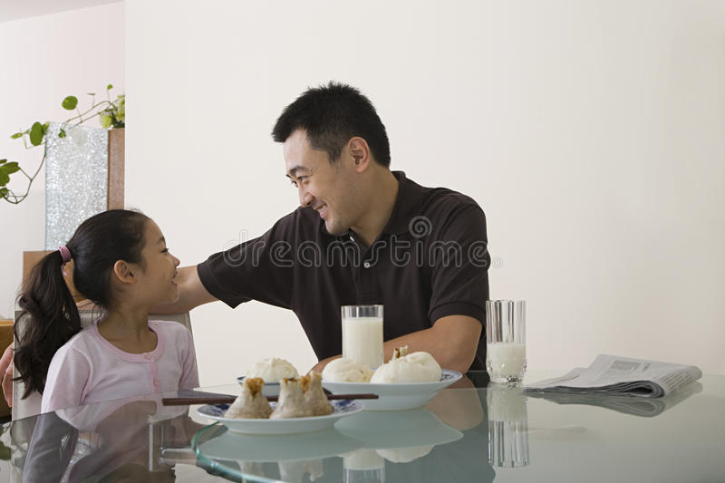Father and daughter sat at a table royalty free stock photography