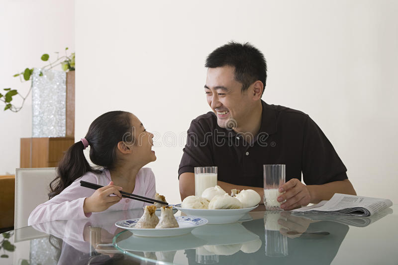 Father and daughter sat at a table stock photos