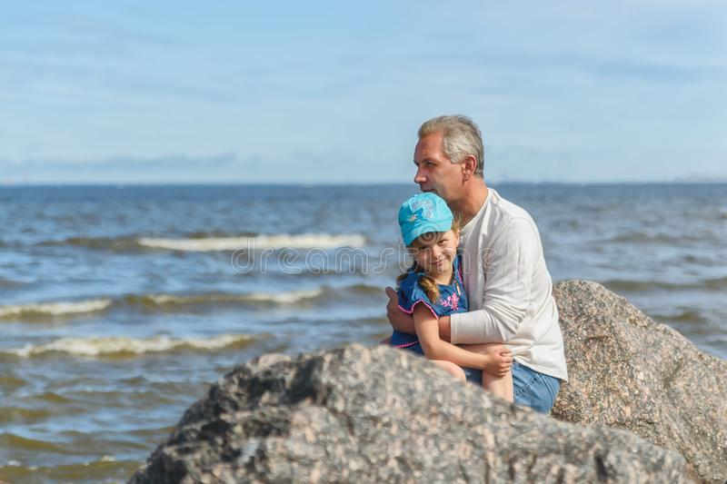 Father with daughter on sea and sky backgrounds. Man and baby are point out forward. Parent and child together at summer. Family, royalty free stock photos