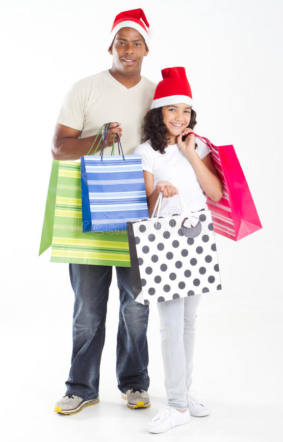Father daughter shopping. Happy father and daughter wearing Christmas hats and carrying shopping bags stock image